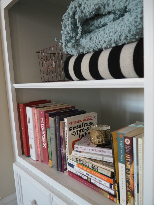 a bookshelf with books and blankets