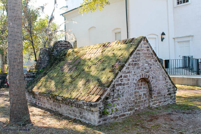 A close up of a stone building that has grass and trees