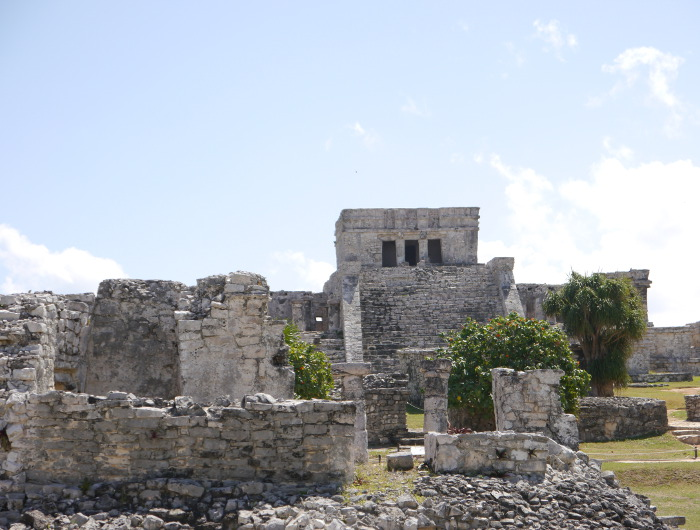 A stone castle next to a rock wall with Tulum in the background