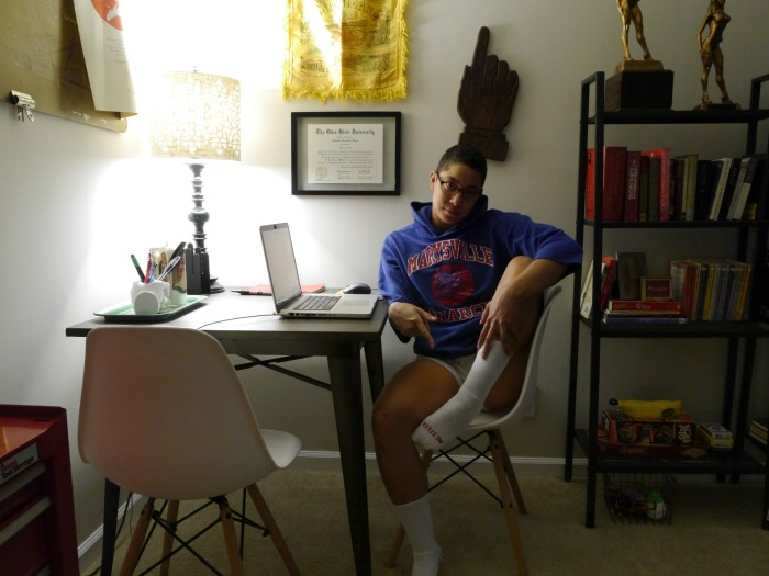 A person sitting at a desk in a small room
