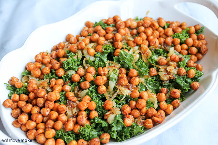 Mustard-Marinated Kale Salad with caramelized onion and spicy chickpeas in serving dish on table