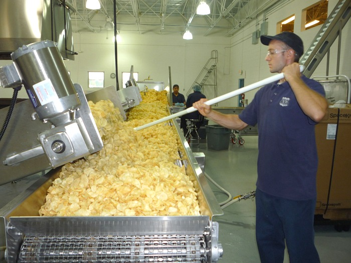 A person preparing potato chips in a pan