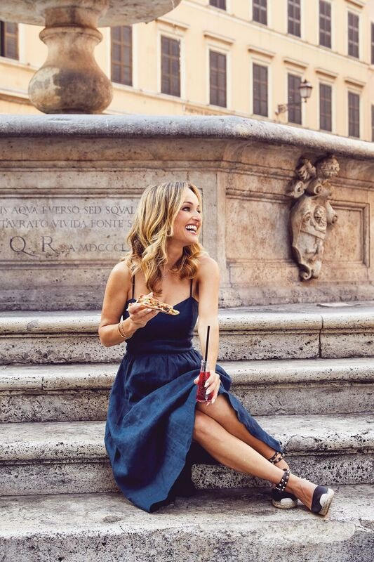 Giada De Laurentiis sitting on a bench in front of a building