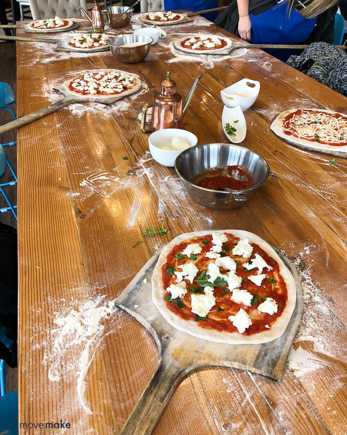 A wooden table topped with plates of pizza