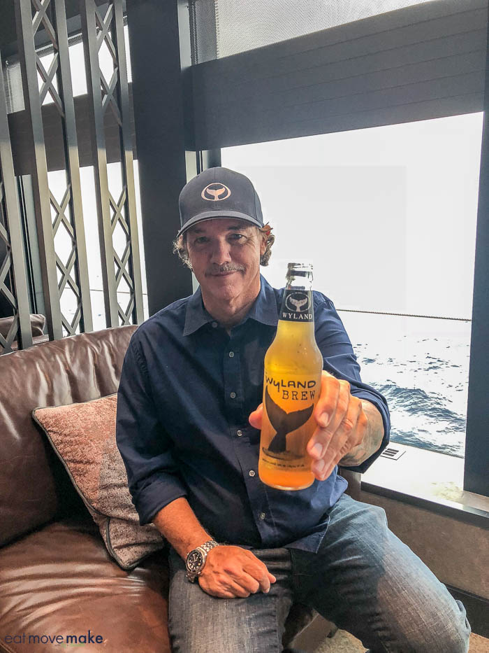 Robert Wyland sitting next to a glass of beer, with Norwegian Bliss and Water