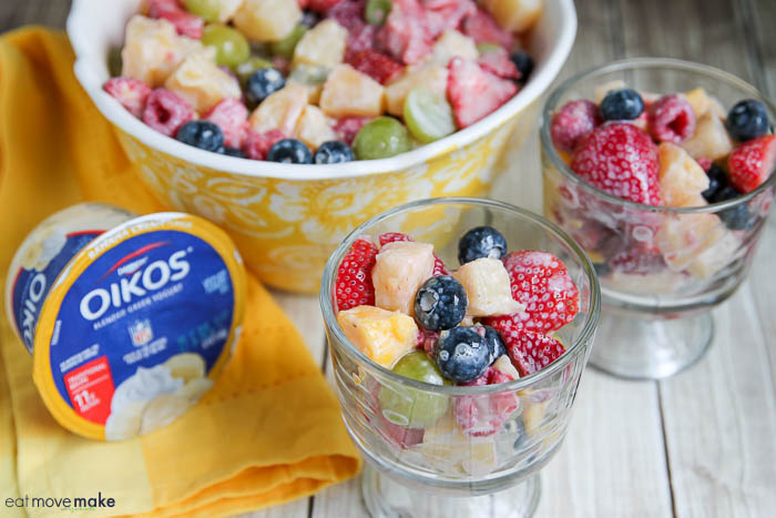 A bowl of fruit on a table with yogurt