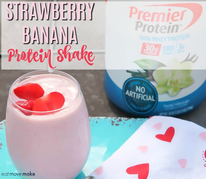 strawberry banana protein shake in glass by protein powder container