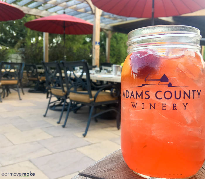 a mason jar cocktail next to a picnic table, with Gettysburg and Adams County