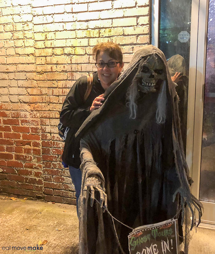 A person standing behind a witch mannequin