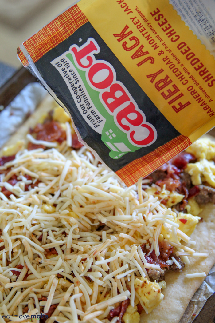 adding cheese to Bacon and sausage breakfast pizza