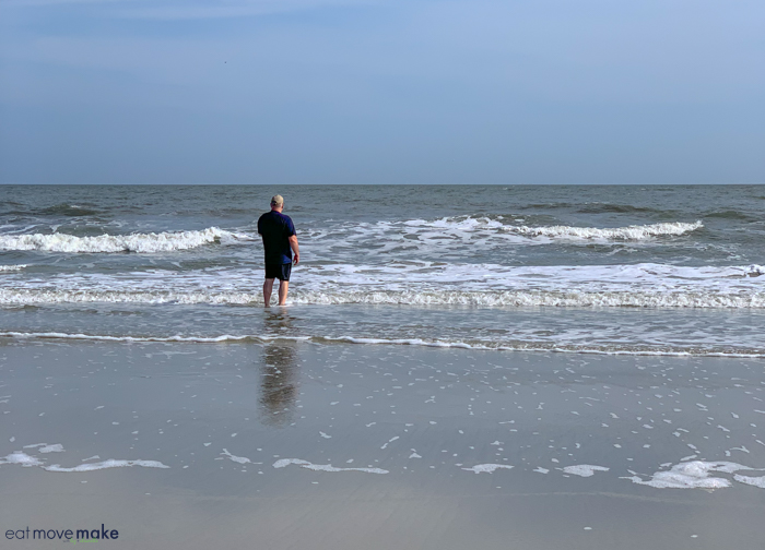 A man standing on a beach next to the ocean, with Hilton Head Island