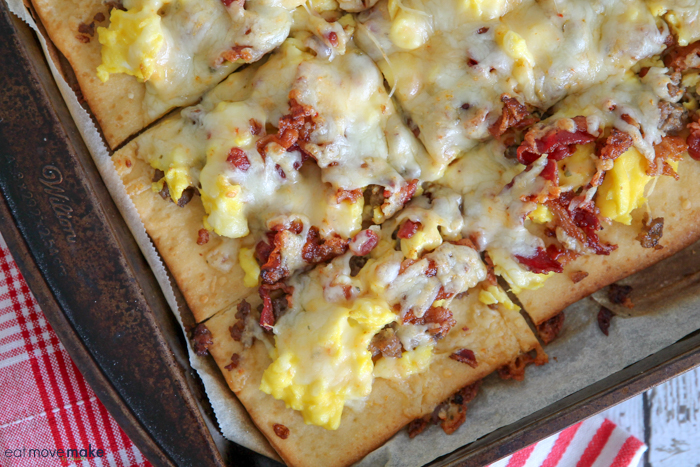 Bacon and sausage breakfast pizza sliced on cookie sheet