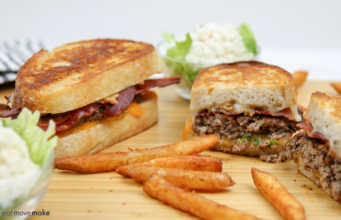 a patty melt and fries on cutting board