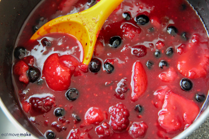 mixed berry compote turning shiny in pan on stove