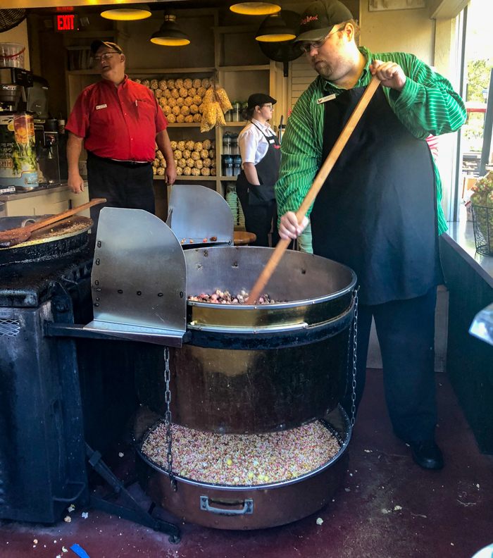 A person cooking kettle corn in a pan