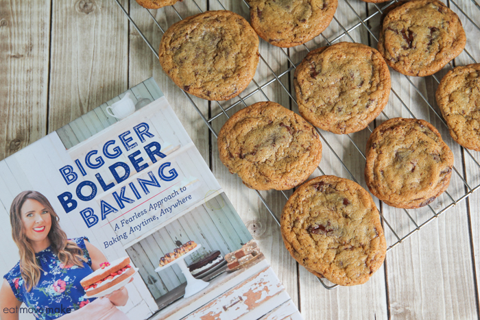 chocolate chip cookies on cooling rack with Bigger Bolder Baking cookbook nearby