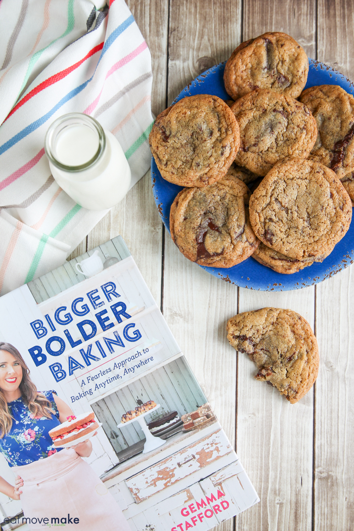 chocolate chip cookies on blue plate with milk glass and cookbook nearby