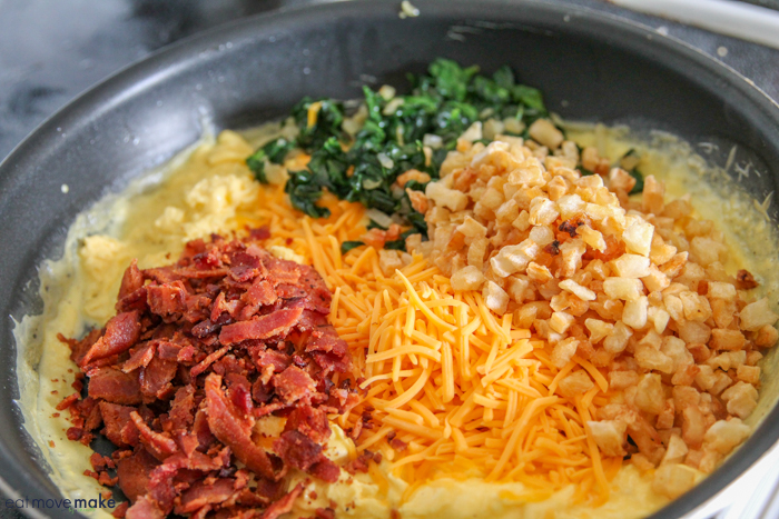 a skillet with spinach, bacon, cheese, diced potatoes, onions and EggBeaters
