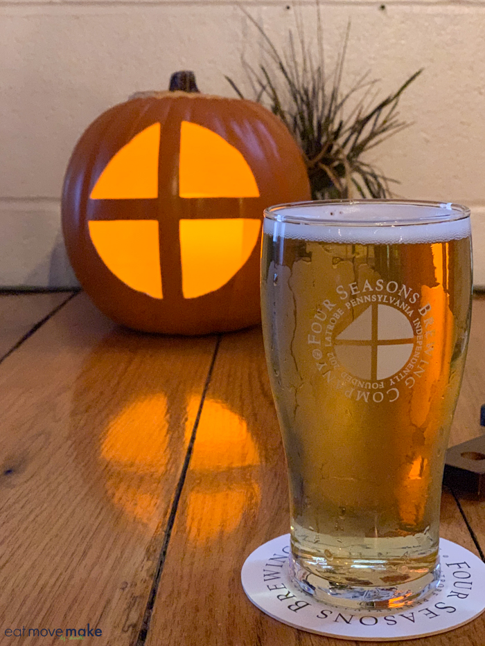 a glass of beer by a carved pumpkin