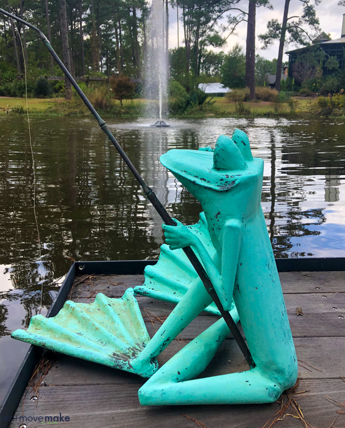 A frog sculpture  by body of water