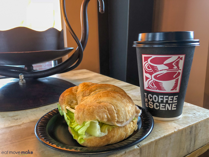 A sandwich sitting on top of a table next to a cup of coffee