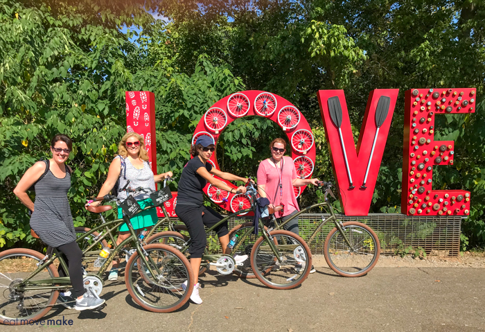 A group of people riding on bicycles by love sign