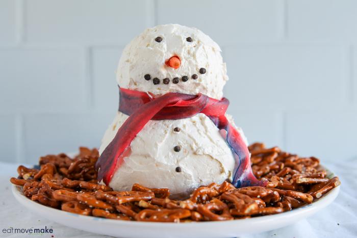 snowman cheese ball on platter with pretzels