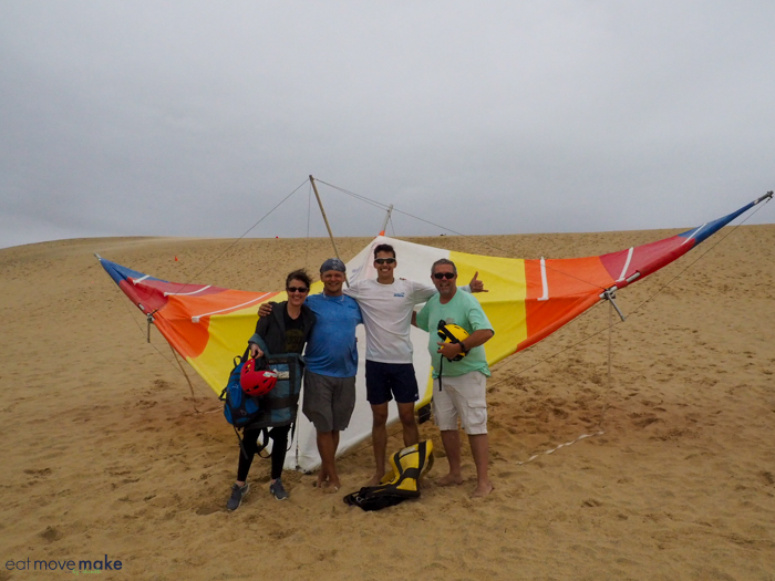 A group of people standing on top of a sandy beach with hang glider