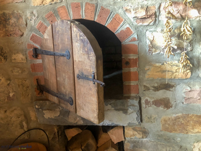 A stone oven next to a brick wall