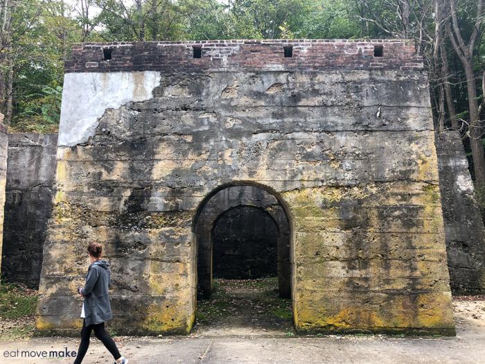 woman walking in front of old  limestone kiln