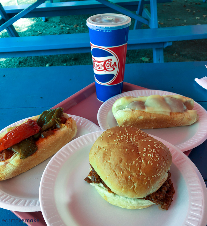 A plate of hot dogs and sloppy joe sitting on top of a picnic table