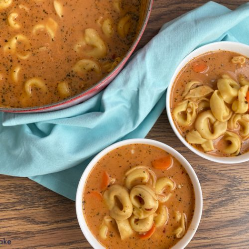 tomato tortellini soup in bowls and in the pot