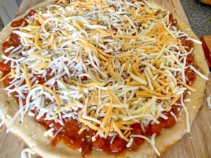 add shredded cheese to pizza