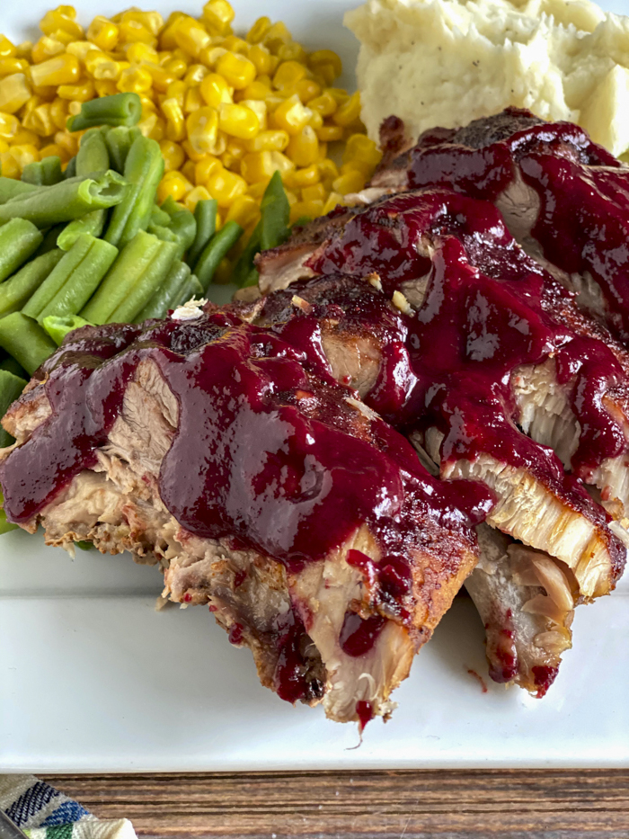 oven baked ribs with blackberry sauce on plate