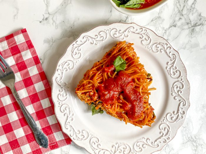 spaghetti pie on plate with sauce on top
