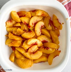 sliced and peeled peaches in white dish