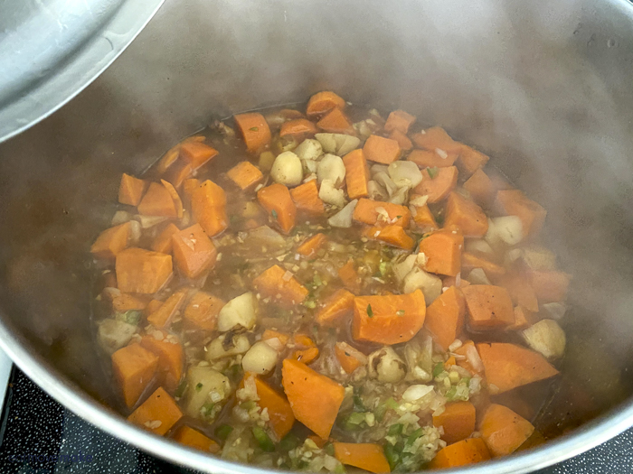 sweet potato and sunchokes in soup broth on stove