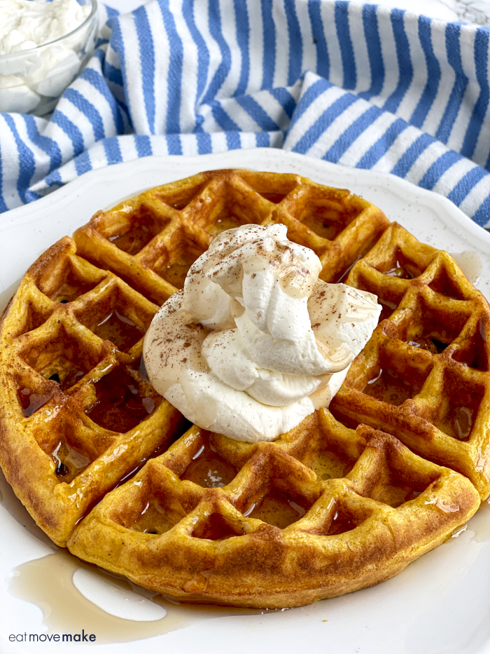 pumpkin waffle on plate with whipped cream and syrup