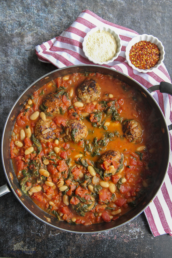 tomato and spinach pasta with meatballs in frying pan