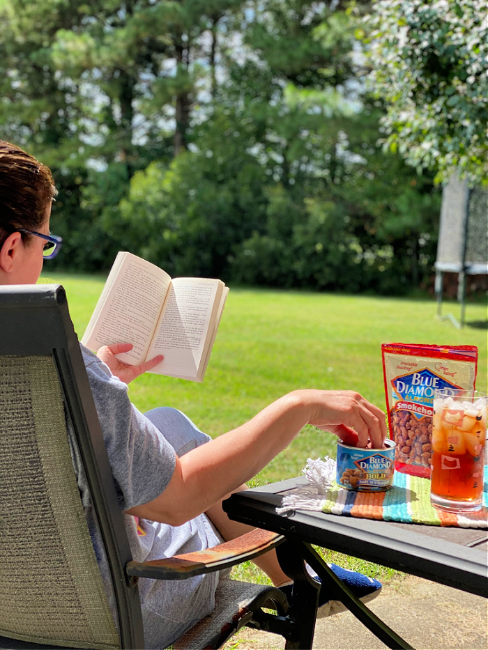 woman eating almonds while reading a book outside
