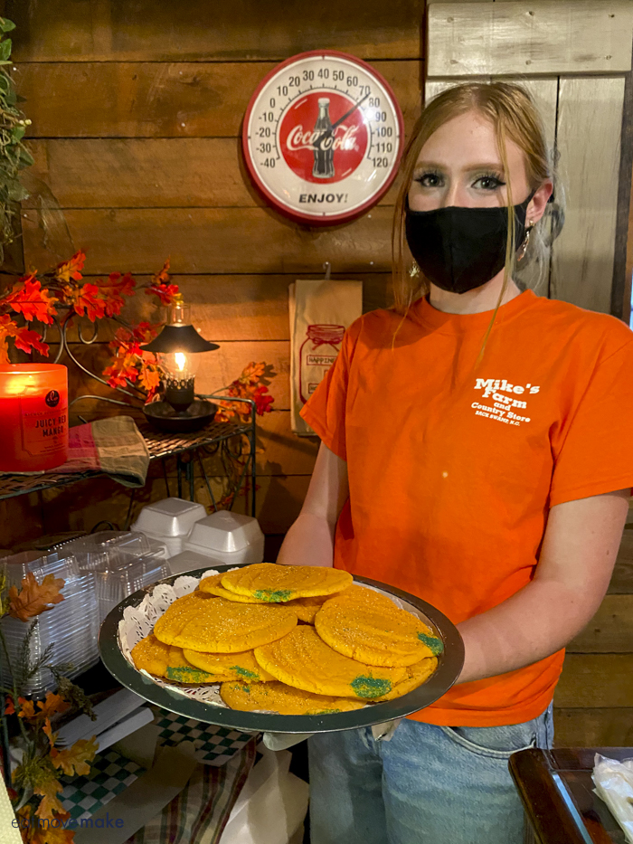 lady holding tray of pumpkin cookies