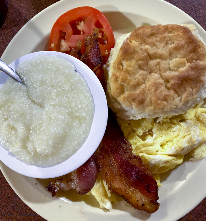 scrambled eggs, bacon, biscuit and grits on plate