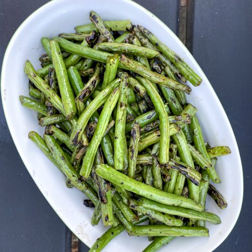 grilled green beans in white bowl