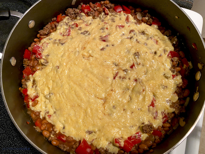 cornbread mixture on top of beef mixture in pan
