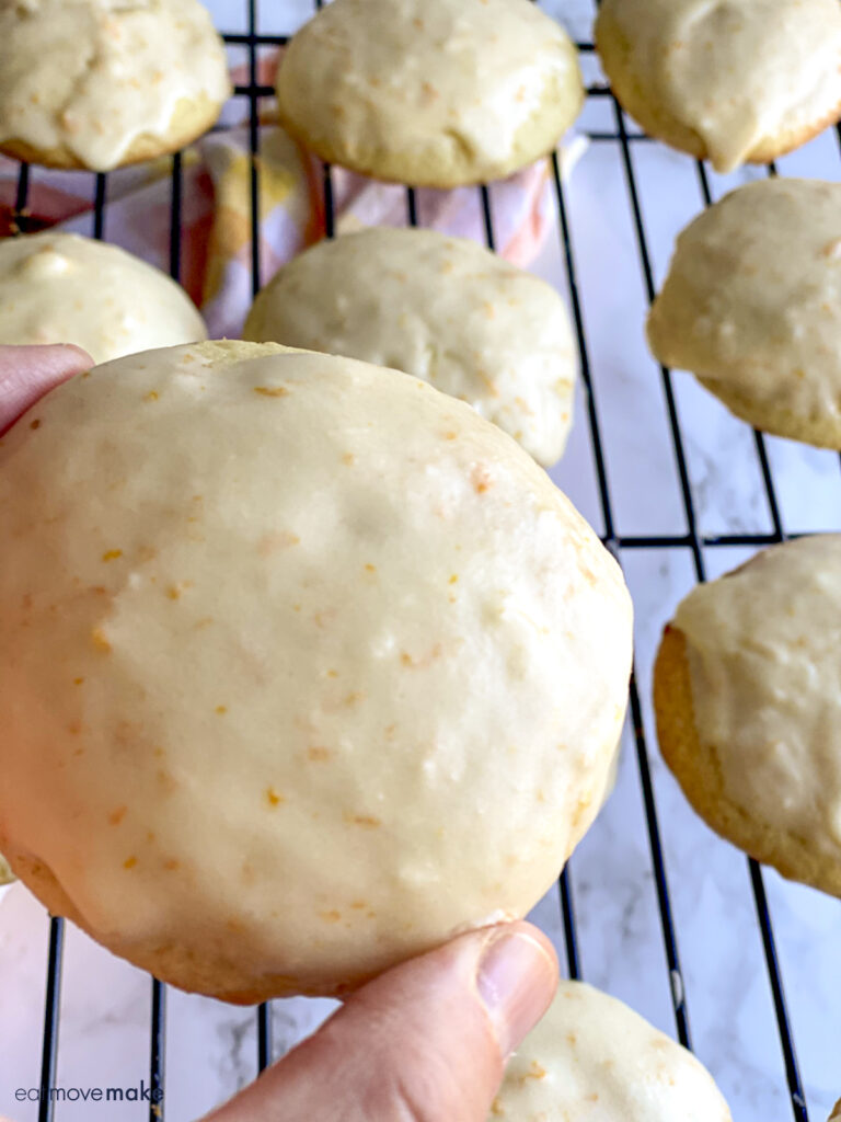 hand holding orange drop cookie with icing