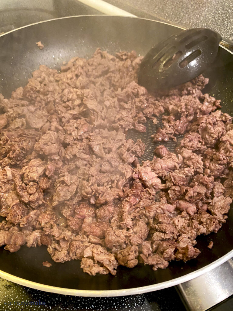 cooking shaved beef in frying pan
