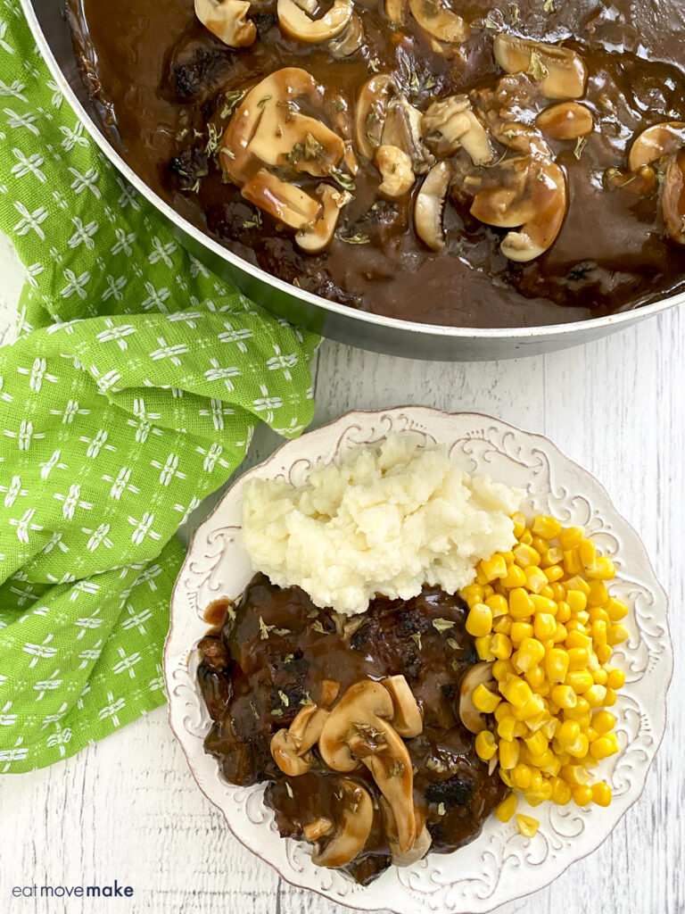 salisbury steak with gravy on plate and in skillet