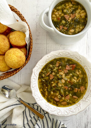 swamp soup in white bowls on white table with basket of corn muffins