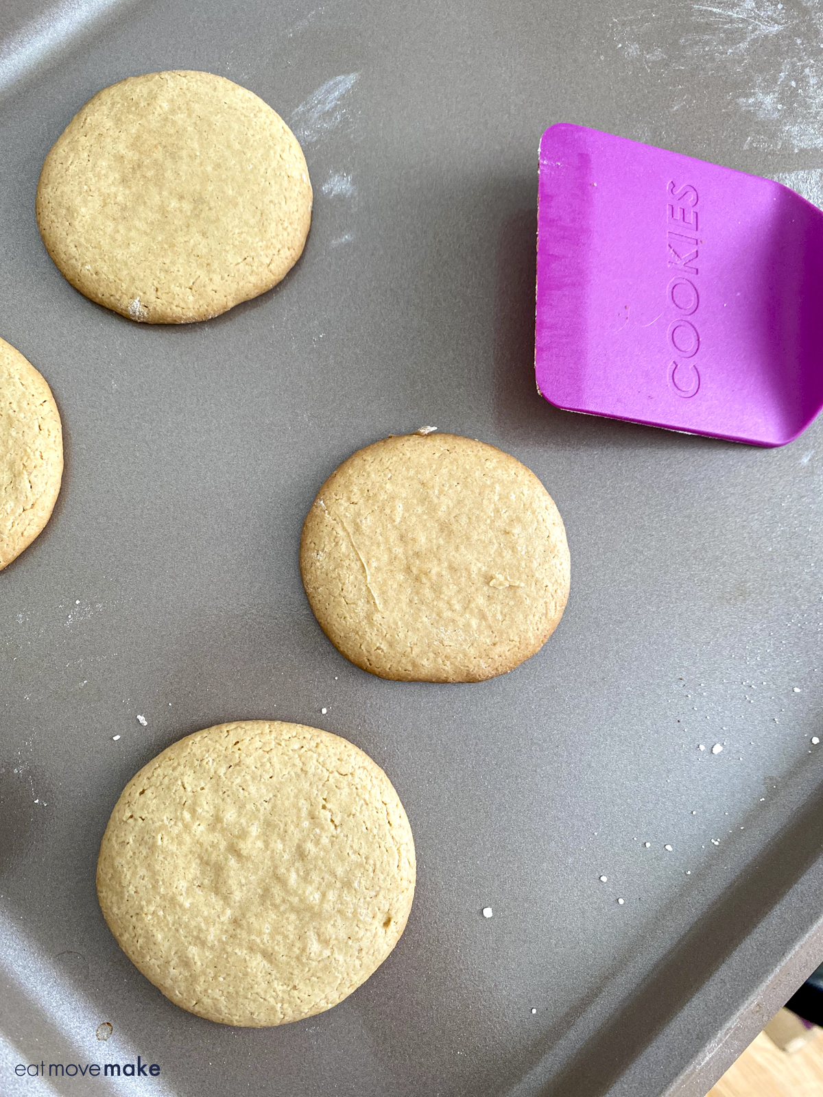 baked cookie rounds on baking sheet with spatula