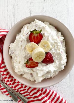 bowl of strawberry banana cheesecake salad with strawberries and bananas on top